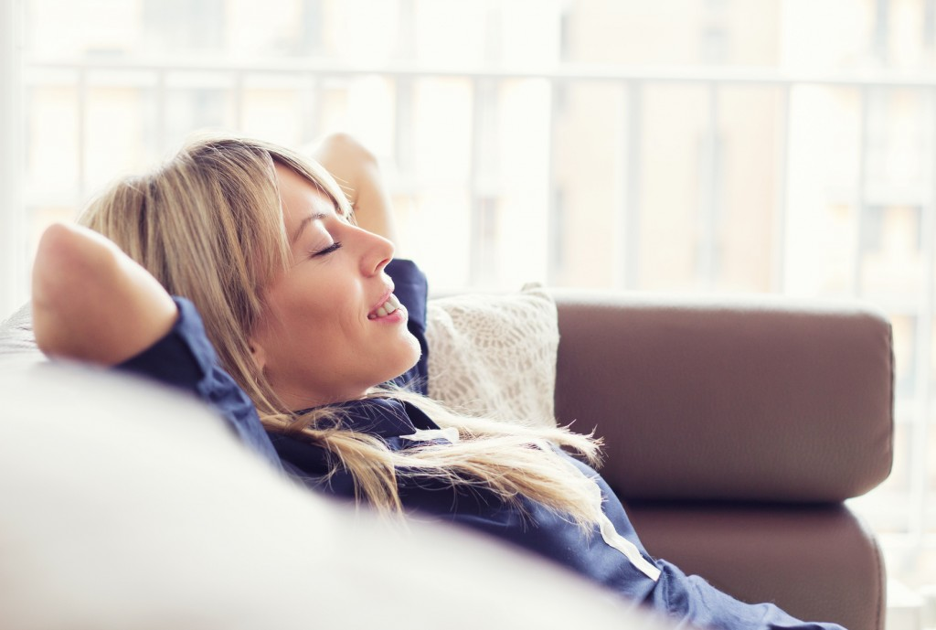 Relaxed young woman lying on couch